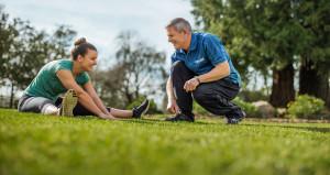 Man coaching a woman while stretching